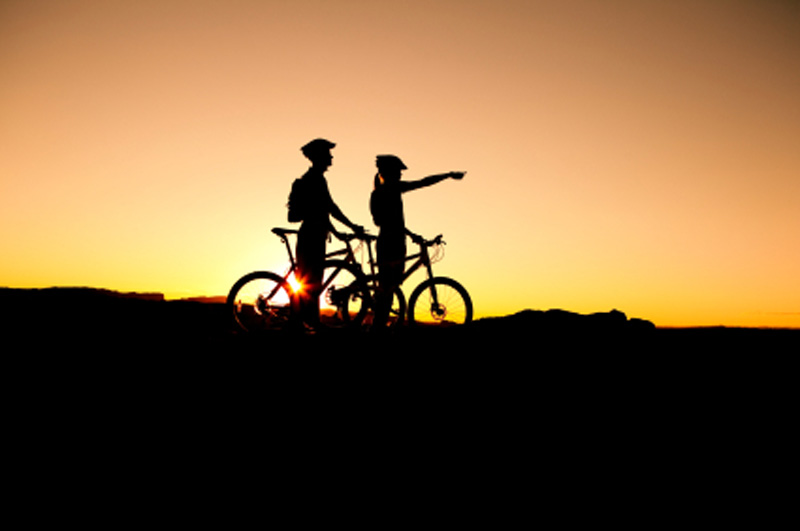 two cyclists at sunset