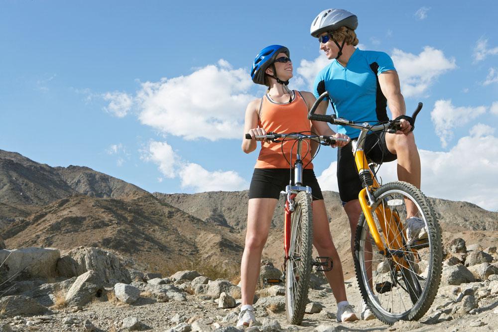 couple mountain biking on mountain bike trail